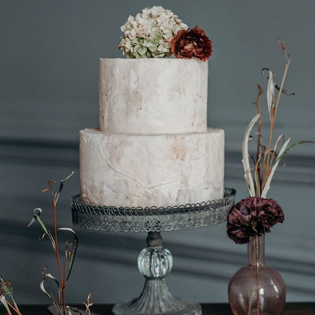 CAKE DISPLAY ///// Beautiful doesn't have to mean super glossy and pretty. The idea behind the Industrial Luxe shoot was a faded windswept beauty. I designed a simple cake display using a beautiful aged cake stand from @boldandbeautifulweddings and this simple textured cake from @sugarmamasdevon @bromptonbuds added some almost dried looking flowers and foliage to complete the look in my little bud vases. . . . . . . Photography @clarekinchinphotography  Venue @greatfulfordwedding…