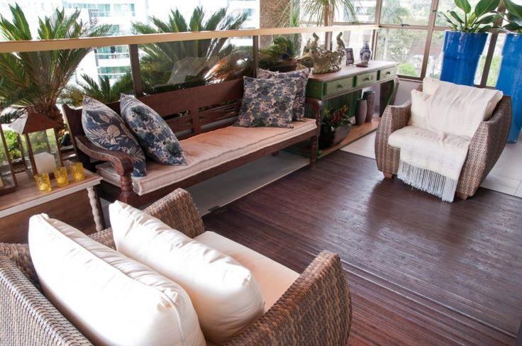 Na varanda, Eliege criou um lounge com móveis em fibra sintética e tapete de madeira, próprios para uso externo - além de um banco de madeira, que foi coberto por um futon bege e recebeu almofadas florais em tons azuis.