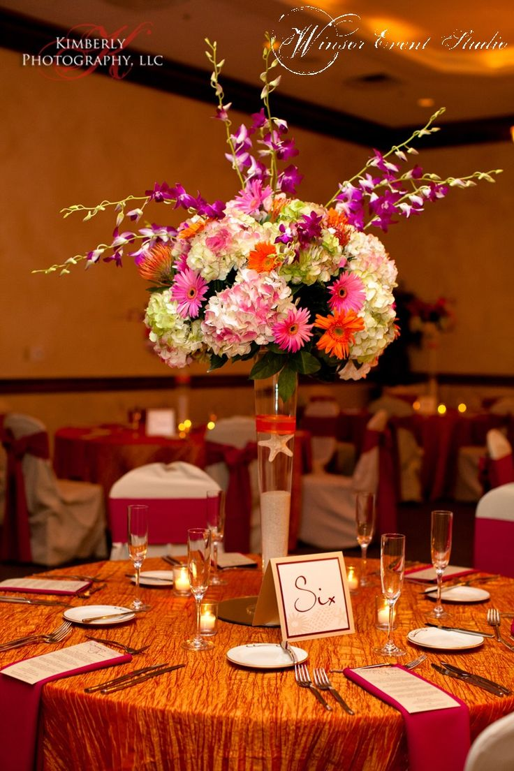 Tall centerpieces of pilsner vases filled with sand and