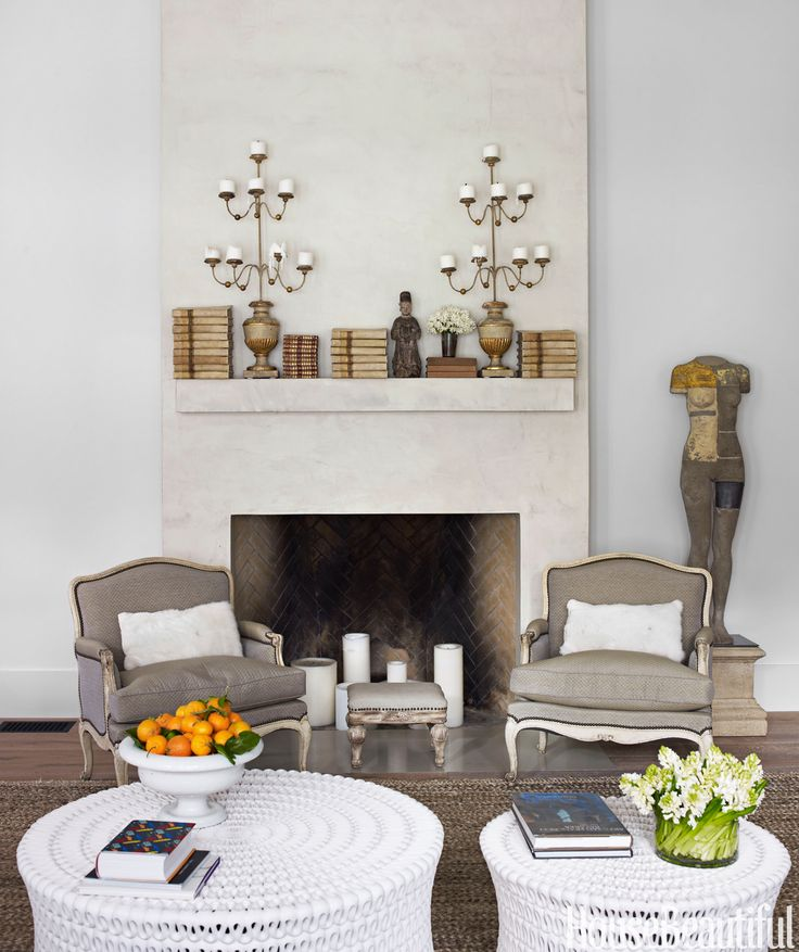 Just because your fireplace doesn't work, doesn't mean it should be in the dark. Placing candles in the space will give it an inviting glow. In a California house designed by Myra Hoefer, white candles in various sizes sit in the fireplace.   - HouseBeautiful.com