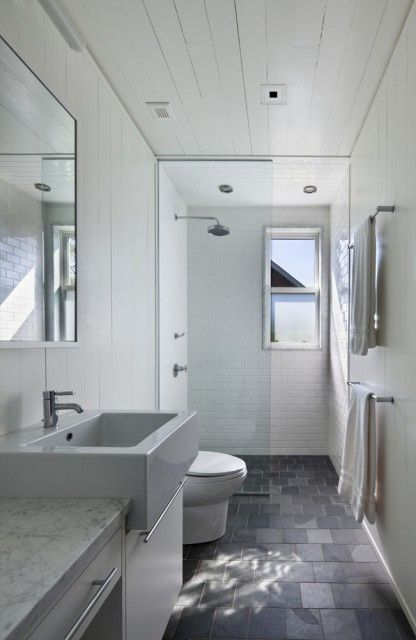 .How a slate/slate look floor looks in a small bathroom. Nice use and placement of the shower stall at the end of this tunnel-like space---the light from the window passes through the glass-enclosed shower into the room itself. Wonders about night showering--do the neighbors get a view?