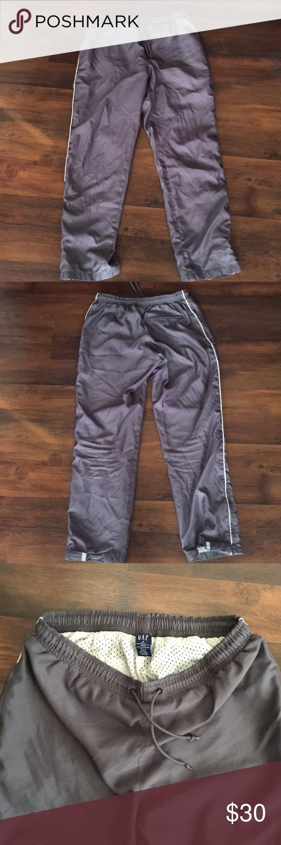 "GAP women's active pants GAP women's active wind pants. The outer shell is very soft and doesn't make the loud ""swish"" and crinkle sound of the old school wind pants.  Inner mesh lining, elastic waist band with drawstring, two side front zip pockets and one zip pocket on the back. The leg bottoms have zippers and adjustable Velcro.  A few tiny dark spots near right side pocket. 2/25/18 GAP Pants Track Pants & Joggers"