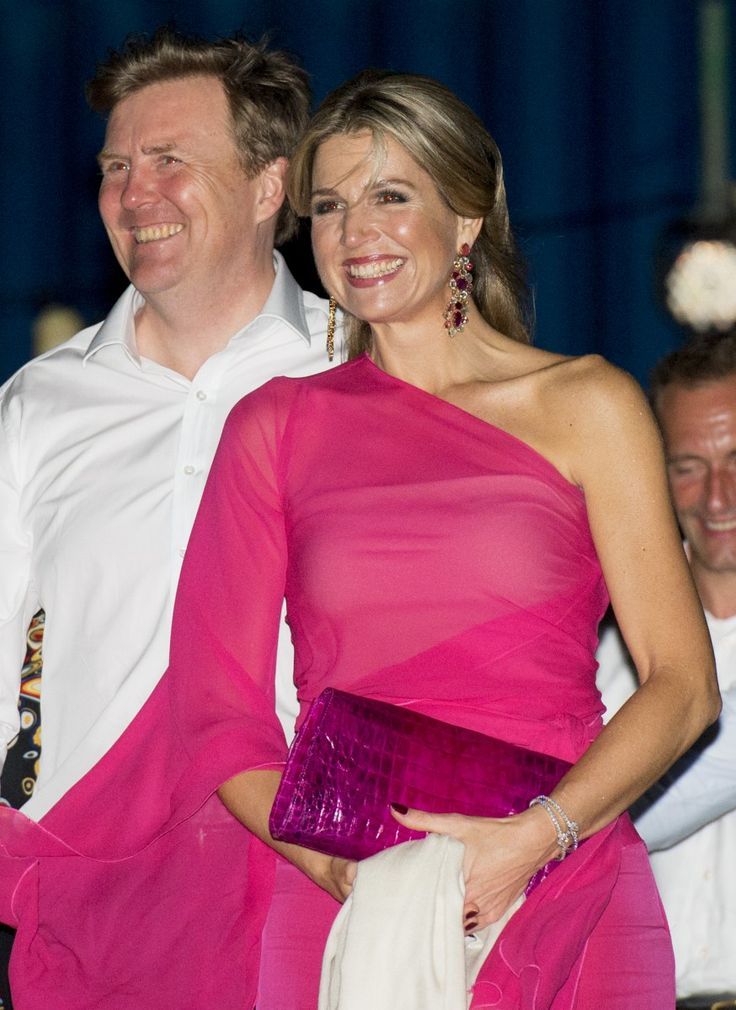 She paired her outfit with a cool crocodile skin clutch in the same hot pink…