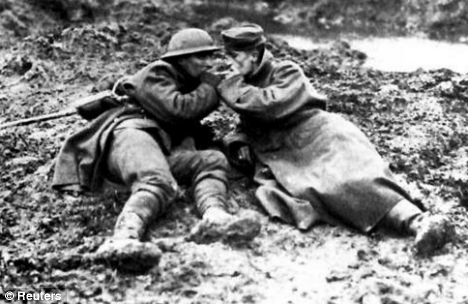 A Canadian soldier lights a German prisoner's cigarette during the First World War at Paschendale on the Western Front, November 1917