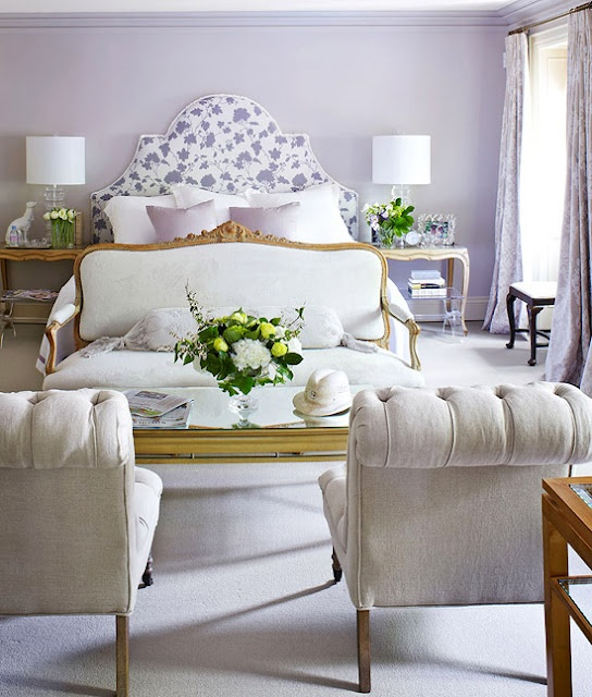 Lilac And White Bedroom With Custom Headboard Includes A Sitting Area At The Foot Of The Bed With Settee Slipper Chairs And Coffee Table