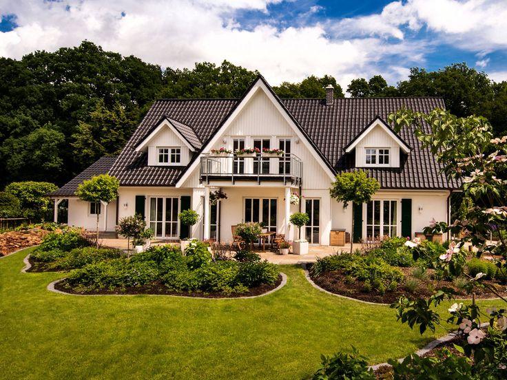 Landhaus von Haacke Haus • Nobles Einfamilienhaus mit großem Zwerchgiebel und vorgeständertem Balkon aus Glas und Stahl • Jetzt bei Musterhaus.net informieren!