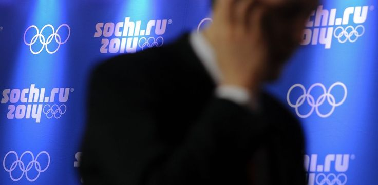 PHOTO: A man uses his mobile phone walking past logos of Sochi 2014 Olympics during a press conference, Feb. 14, 2012, in Krasnaya Polyana.