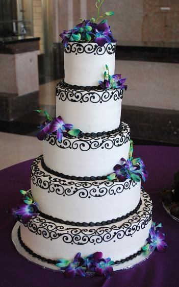 blue orchid on five tier cake with upper black piping