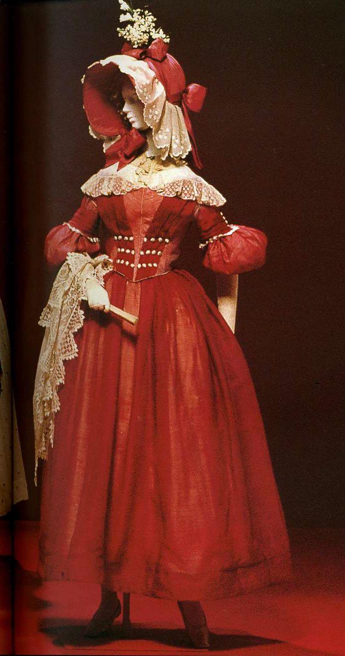 Дневное платье. Около 1838. Смесовый газ из красного шелка и шерсти с отделкой кантом из шелкового атласа, пуговицы на корсаже и рукавах, обшитые материалом, рукава gigot, украшения из складок и вставка блондового кружева на плечах.