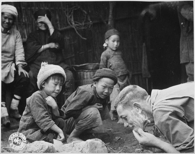 Two young boys in Yunnan, China, astutely observing an American soldier as he shaves. 1944.