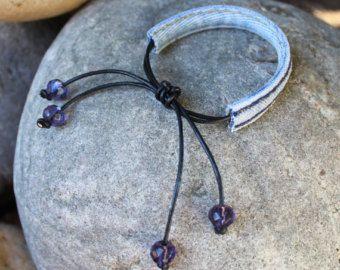 Pulsera del dril de algodón con cuentas de cristal púrpura y tire de cuero negro 251025347