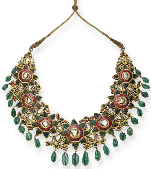 A DIAMOND, EMERALD AND ENAMEL NECKLACE   Designed as seven floral panels set with table-cut diamond and foiled red gem centers, extending carved emerald leaves within foiled surrounds to the emerald bead fringe, the polychrome enamel reverse depicting foliate motifs, on a metallic silk cord. Indian or Indian style