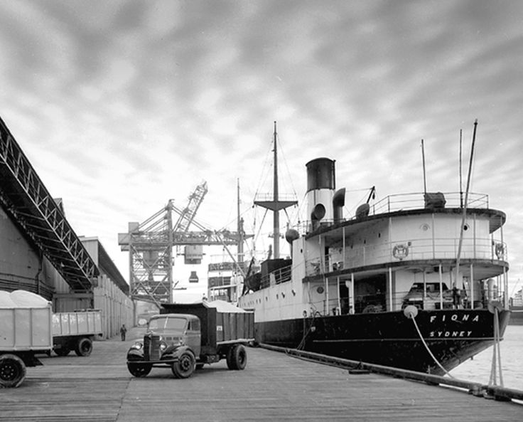 Pyrmont sugar refinery wharf with trucks loading sugar from ship Fiona, crane in background, June 1955. Max Dupain photo.
