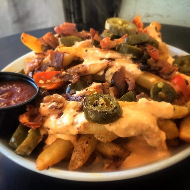 The Secret Sandwich Society's loaded pimento cheese fries have melted homemade pimiento cheese, bacon and jalapeños.