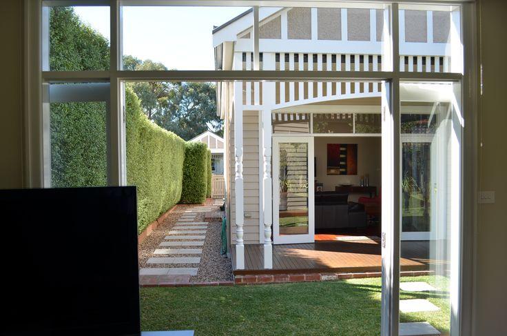 Traditional house renovation. Fretwork.  Verandah. Neutral scheme.  Landscaping.  Hedges.  Stepping stones. Lisa Banducci Design.