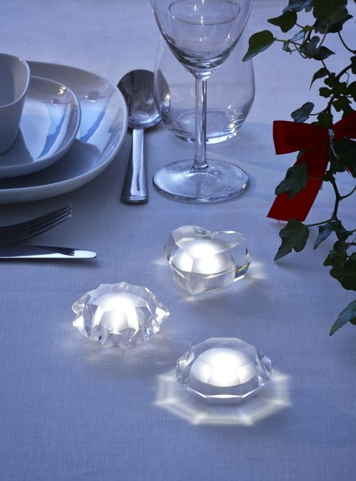 The soft glowing light of a STRÅLA decoration warmly welcomes guests to a dinner table