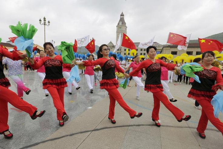Local residents dance during a rehearsal for a possible upcoming celebration event on Friday afternoon, at a square in Chongli county of Zhangjiakou, which is jointly bidding with the capital Beijing to host the 2022 Winter Olympic Games, July 30, 2015. The bidding committee plans to use many of the buildings that hosted events in 2008 for the indoor ice events in 2022, but the outdoor events present more problems. REUTERS/Jason Lee