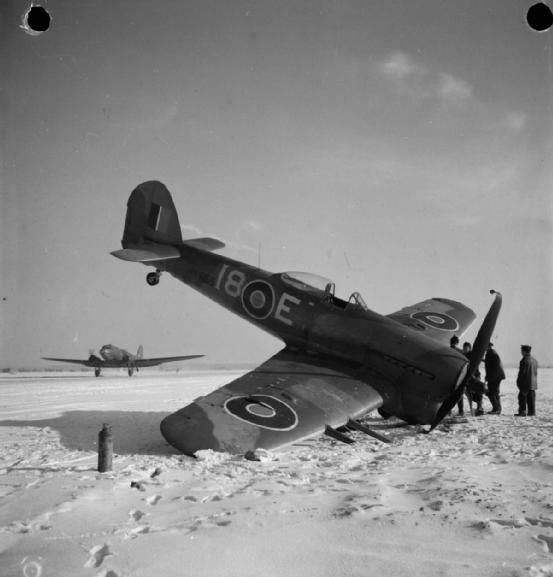 Unintended work of art - A Douglas Dakota of RAF Transport Command lands at snow-covered B78/Eindhoven, Holland, as ground crew inspect Hawker Typhoon Mark IB, MN659 'I8-E', of No. 440 Squadron RCAF, which suffered a collapsed undercarriage on landing after a sortie.