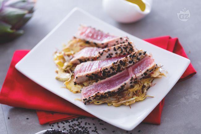 Il tonno al sesamo è un secondo piatto di pesce fresco e raffinato: tonno impanato con semi di sesamo, scottato e servito con carciofi crudi.