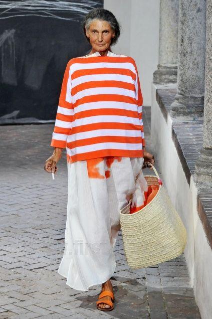 Daniela Gregis. con falda blanco y jersey a rayas naranja y blanco. sandalias naranjas