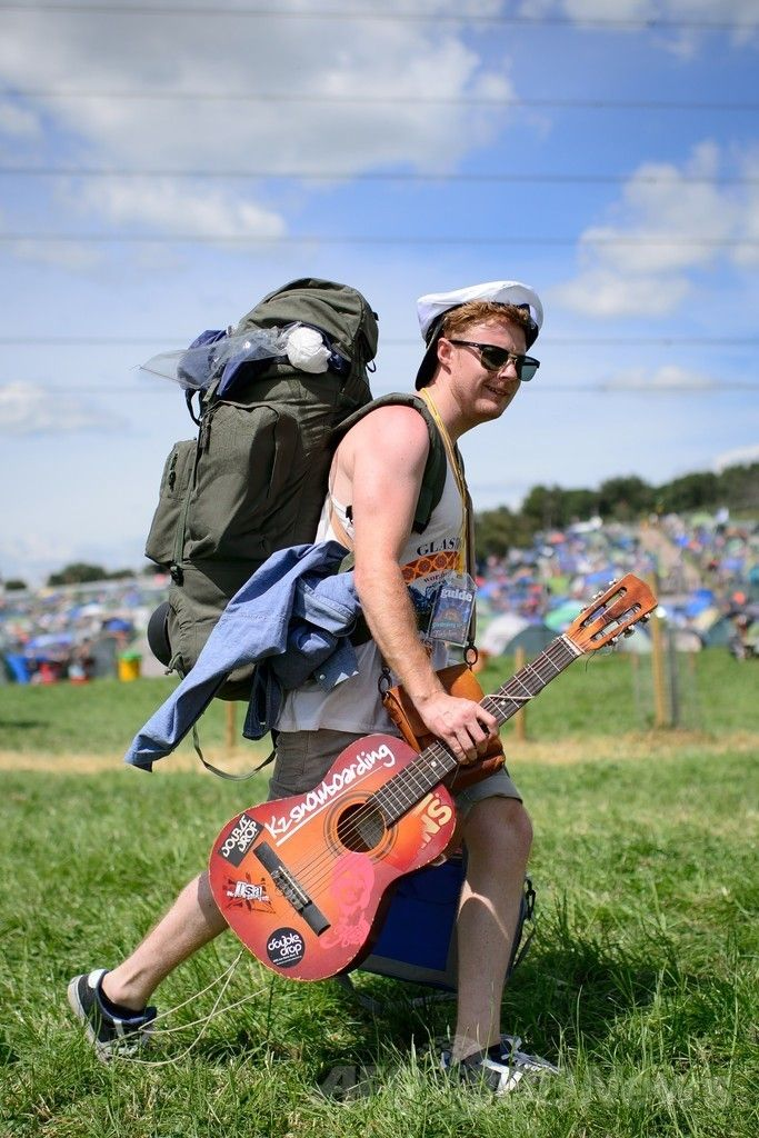 英南西部サマセット(Somerset)州ピルトン(Pilton)で開幕した世界最大級の野外音楽祭典「グラストンベリー・フェスティバル(Glastonbury Festival)」の会場にテントとギターを担いで到着した参加者(2014年6月25日撮影)。(c)AFP/LEON NEAL ▼27Jun2014AFP|世界最大の英野外音楽祭「グラストンベリー」が開幕 http://www.afpbb.com/articles/-/3018900 #Glastonbury_Festival