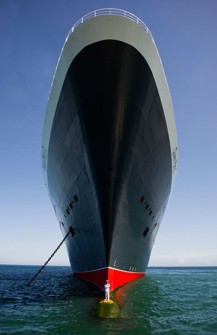 Captain stands on bulbous bow of queen marry 2.  Worst part is... Some poor deckhand had to go out there and clean the slime and marine growth off to make a nice clean spot for the Captain to stand on for the pretty picture.  Remember to support your local deckhands anonymous organization.