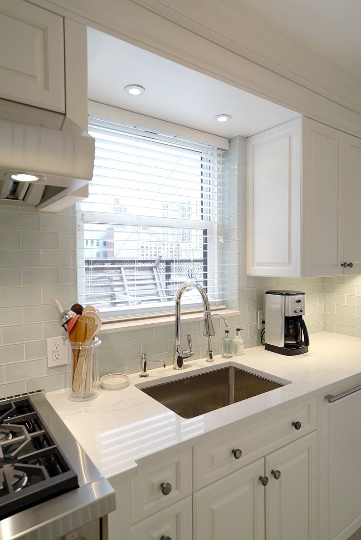 A custom galley kitchen meets its match! The spectacularMichael Bermanfaucet from Rohl pairs seamlessly with a Nemo Tile backsplash, Franke basin andCaesarstone countertop. | Paula McDonald Design Build & Interiors