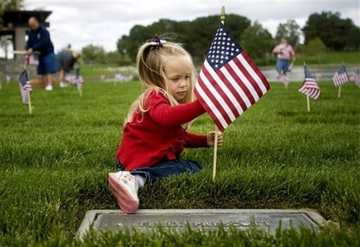Mackenzie Griffith, 3, decorates a grave with a flag in honor of Memorial Day.