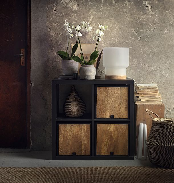 Square-shaped baskets made of coconut palm leaves, shown in a black-brown shelving unit.