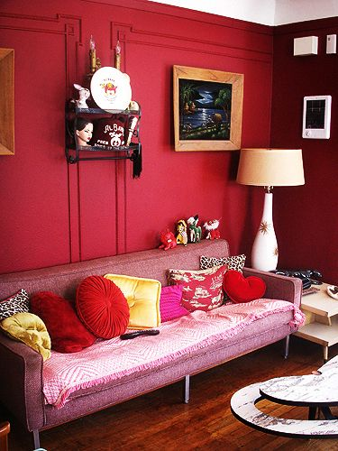 Adore the rich berry red walls and colour pop cushions in this glam space.