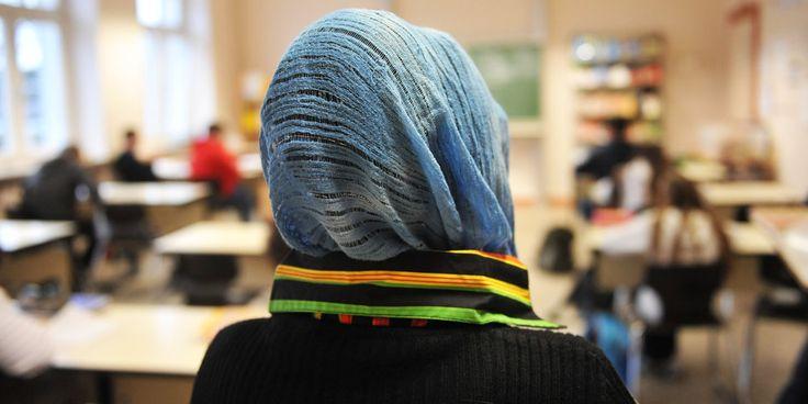 Eine Frau mit Kopftuch von hinten in einem Klassenzimmer