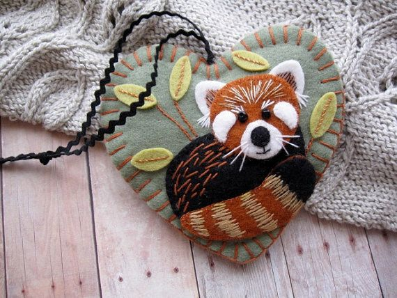 I had so much fun making this adorable red panda ornament. Isnt he the cutest, all curled up in his favorite bamboo patch! I used top quality 100% wool felt in greyish green, white, rust, yellow green, and black, with embroidered details in black, rust, white, and golden tan cotton floss. The ornament is plumped out with polyester craft batting and features a black baby rick rack hanging cord. It measures approximately 4 1/4 in both length and width. The Red Panda ornament was handmad...