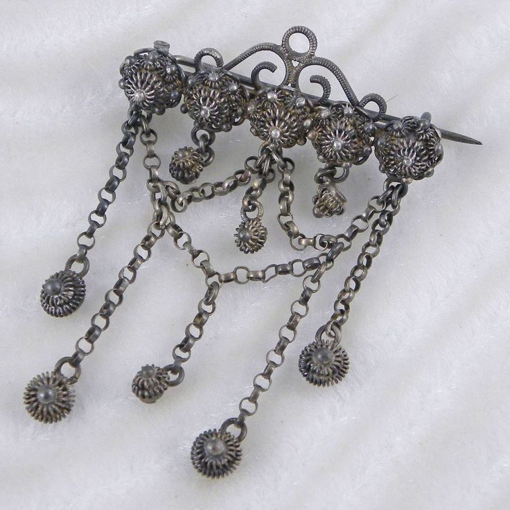"An unusual and rare victorian pin featuring delicate wire work components and thin rolo style chain dangles. The back has a tube hinge pin with wire c-clasp. The metal is a patina-ed dark gray. Possibly steel? The pin measures 2 3/16"" wide by 2 3/8"" long."