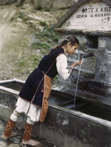 A young girl wears hand-stitched leggings at a fountain.   Location: Florina, Greece.  Photographer: B. ANTHONY STEWART/National Geographic Creative