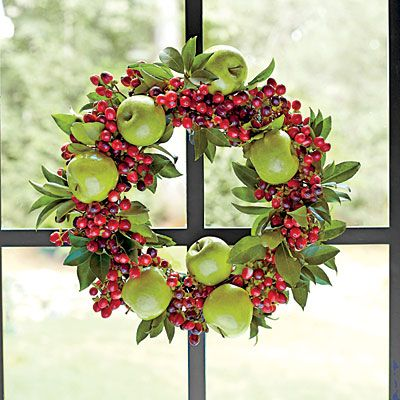 Traditional Colors | Every home needs a touch of red and green during the holidays. This year, we freshened the typical motif with a shapely wreath made from real Granny Smith apples wired to a florist foam wreath form with florist picks. Red hypericum berries and bay leaves fill out the rest of the wreath.