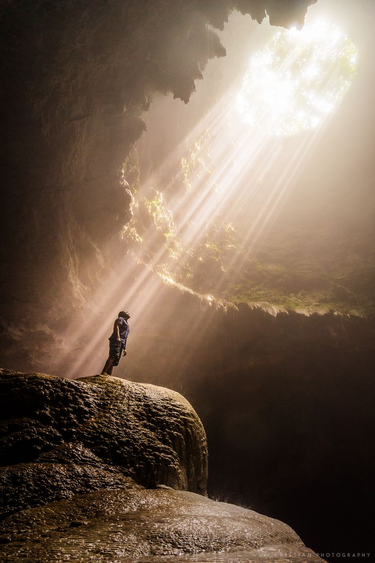 Sunbeams illuminate the vertical cave of Grubug, which is accessible only by descending about 60 meters by rope through Jomblang, another nearby vertical cave in Central Java, Indonesia. The two caves are separated by a 300-meter underground alley. The light beams form naturally between 10am to 12pm and has become the main attraction for exploring the twin caves.