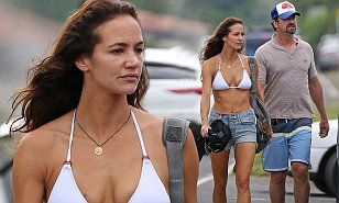 Gerard Butler's girlfriend Morgan Brown turned heads as she showed off her taut frame in a white triangle bikini top with cut-off denim shorts during a recent romantic break in Hawaii.