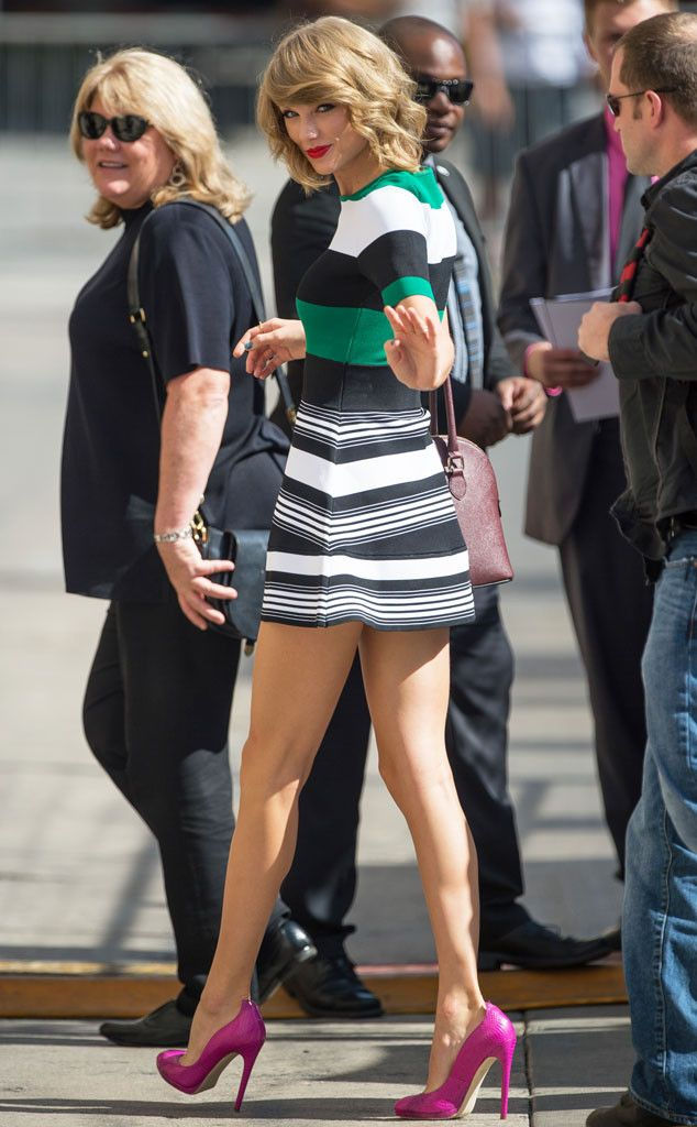The Wave from Taylor Swift's Street Style  Hey, Tay! The pop star gives a quick wave rocking a striped mini dress and magenta pumps.