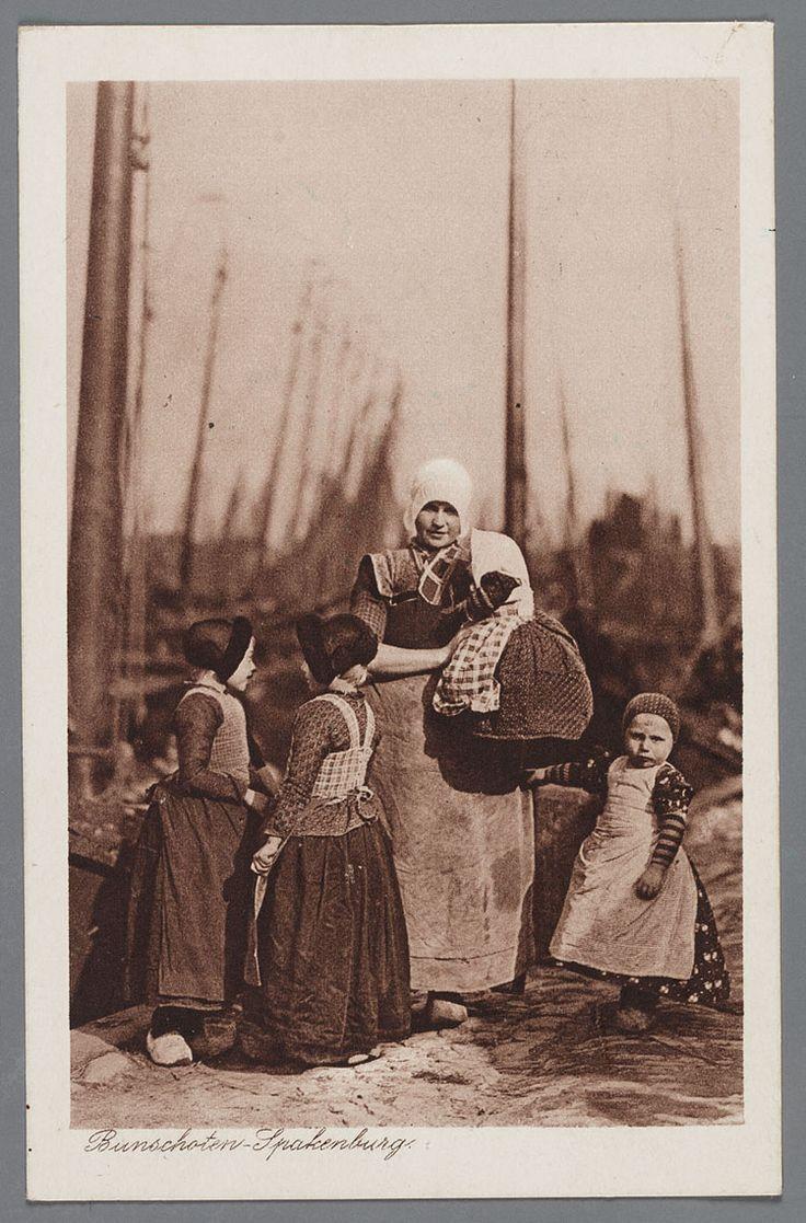 Bunschoten Spakenburg Vrouw en kinderen in de haven. Een staande jonge vrouw met kanten muts, korte kleine kraplap, ongedeelde rode doek, donkere kraplap en donkere geruite boormouwtjes, effen werkschort en klompen. Op de arm een kindje met wijduitstaand jurkje met fries schort en gebreide mofjes op het hoofd een wit hoofddoekje. Rechts van haar een jongen in rokken met klapmuts en gebreide mofjes. Links van haar 2 meisjes met jak en lieffiessjullek en pluummuts. 1910-1930 #Utrecht…