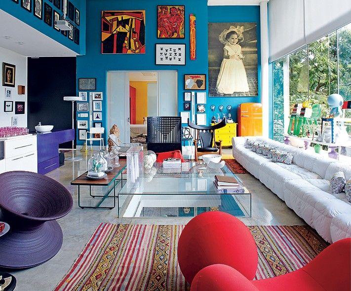 Na sala com pé-direito duplo, impressiona a quantidade de peças de design do arquiteto Leo Romano, expostas como obras de arte. O profissional coleciona cadeiras, como a Willow e a Chifruda. A cor do ambiente  é o azul petróleo