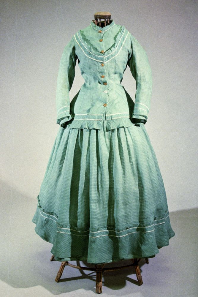 Dámské vycházkové šaty strojově a ručně šité ze zelené bavlněné tkaniny s vytkaným zesíleným proužkem. Prodloužený vypasovaný kabátek s malým stojacím límečkem, vpředu se zapínáním na osm knoflíků, v hrudní části do oblouku aplikovaný, bíle lemovaný pás s nabíraným volánkem. Zadní díl princesového střihu ve švech s bílými paspulkami. Dlouhé úzké rukávy a spodní okraj kabátku zdobí lem s volánkem. Sukně v pase nabíraná, u spodního okraje s volánem. Živůtek podšitý béžovým bavlněným plátnem.