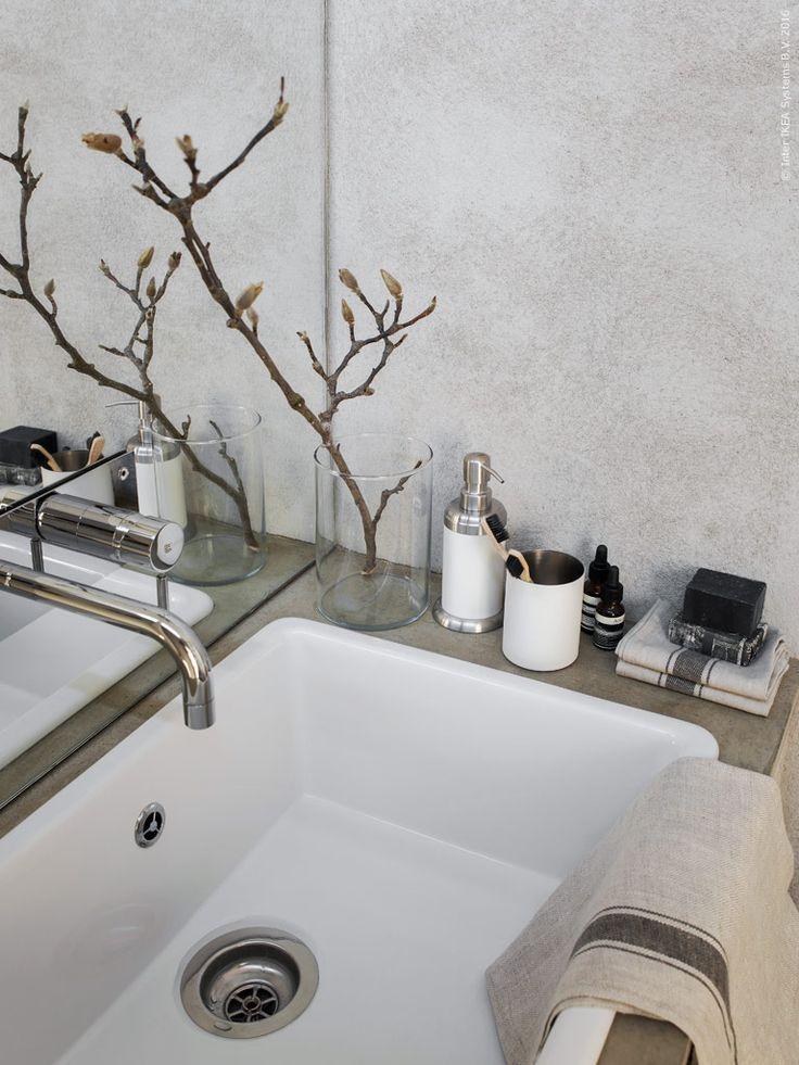 Här fungerar inbyggnadsdiskbänken DOMSJÖ, som ett generöst handfat nedsänkt i en betongskiva. En magnoliakvist bildar ett vackert blickfång i den enkla vasen CYLINDER. De nya linneservetterna i serien VARDAGEN, fungerar utmärkt som tvättlappar eller gästhanddukar i badrummet.