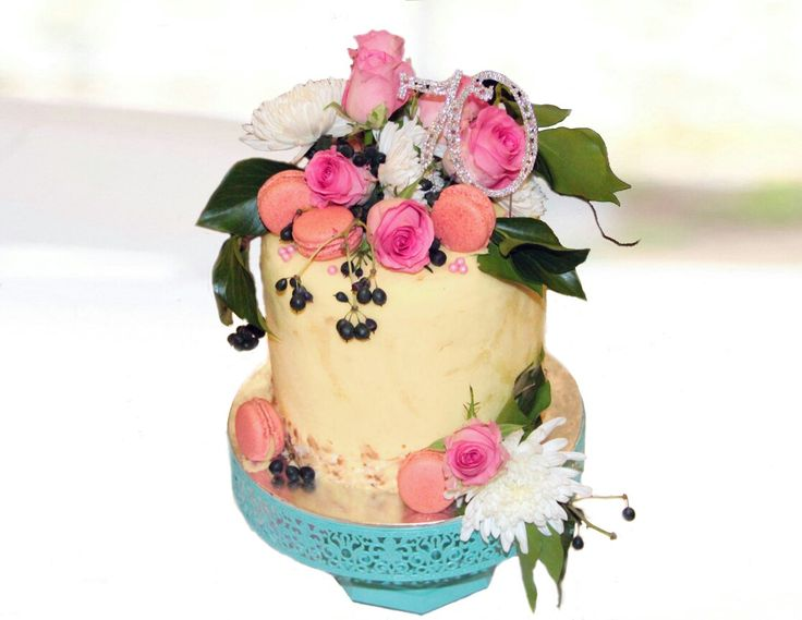 A beautiful Coconut Cake layered with Strawberry Cheeseake and covered with creamy Buttercream, fresh flowers and macarons!   Simply delicious!