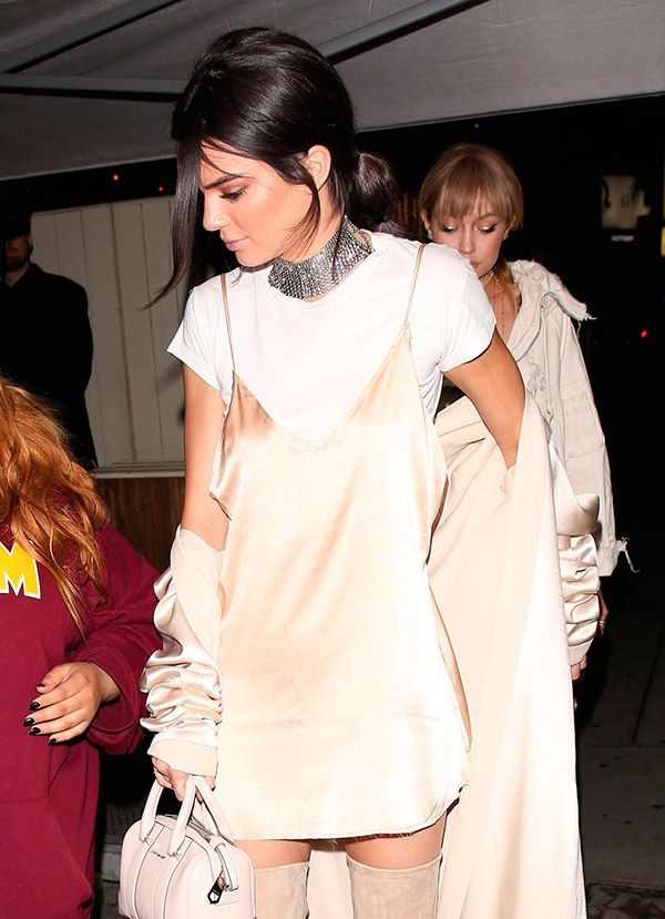 Kendall com slip dress, camiseta branca, bota OTK e choker prata.