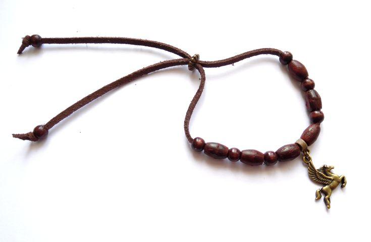 Armband i brun mocka med detaljer i brons och bruna träpärlor.  Armbandets…