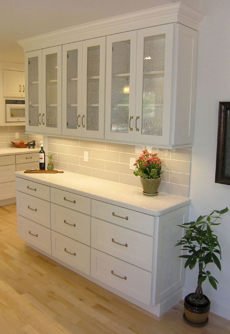 shallow buffet built of white shaker cabinets with textured glass doors and sash pulls
