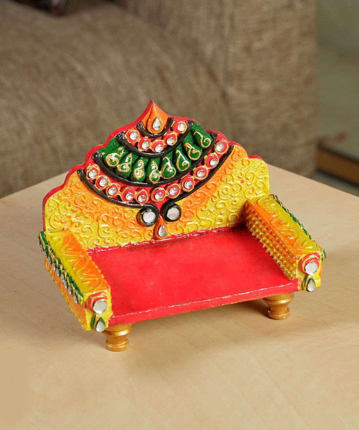 A miniature hand painted chowki throne with kundan work. The chowki comes with scroll Clay work and painted in hues of orange. The Throne back is inlayed with traditional clay work and studded with kundans for a Regal look.