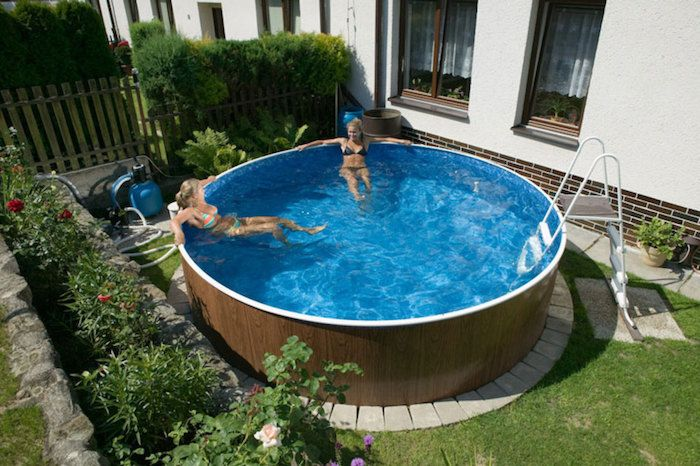 Small Above Ground Pools Two Women Lounging In A Round Pool Blue Inside And Covered In A Wood Like Material O In 2020 Small Backyard Pools Backyard Pool Small Backyard