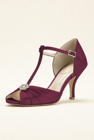 """With a nod to era's past, this t-strap pump by Pink Paradox is a must-have for any vintage-inspired occasion!  Beautiful t-strap peep toe pump features pleating on the vamp and a delicate pearl and crystal broach. Special memory foam padding makes this style extra comfortable.  Heel Height: 2.75"""".  Imported."""