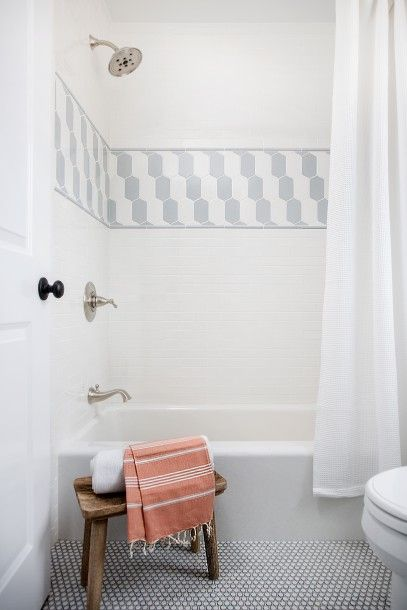 White penny tiles contrasted with black ground frame a drop-in bathtub covered with a white shower curtain and fitted with a satin nickel tub filler and shower head mounted on white subway backsplash tiles accented with gray and white border tiles.